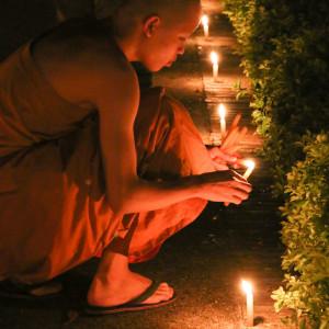 蝋燭に火を灯す僧侶